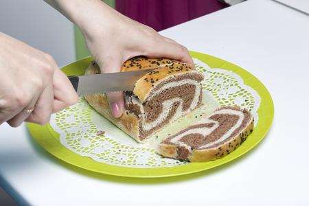 Woman cuts fresh ruddy bread. The slice shows cocoa blotches. Reklamní fotografie - 117066613