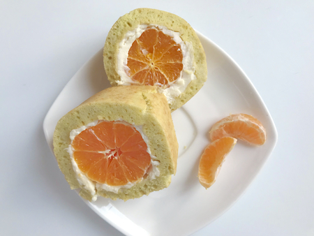Cooking biscuit roll stuffed with ricotta and mandarin. Ready roll lies on a platter. Next on the saucer is a cut piece of roll.