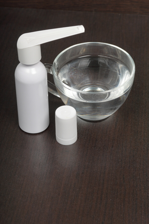 Inhaler for the treatment of respiratory organs. Spray can and cap white. The tip is soaked in water from drying. On a dark surface.