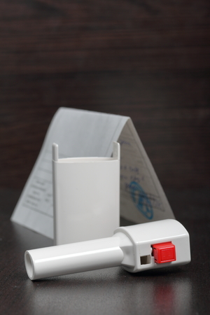 Inhaler for the treatment of respiratory organs. Spray can and cap white. Next recipe to buy. On a dark surface. 版權商用圖片