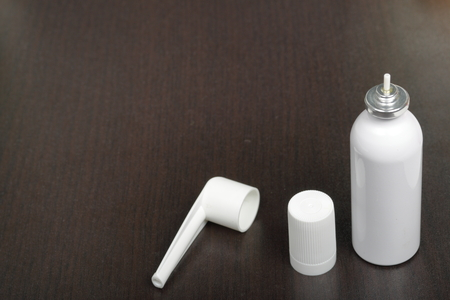 Inhaler for the treatment of respiratory organs. Spray can and cap white. On a dark surface.