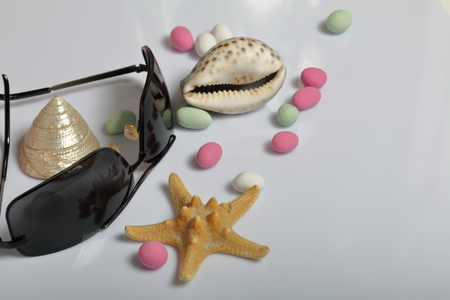 Summer holiday accessories. Colored pebbles, seashells, sunglasses and starfish on a white background. Zdjęcie Seryjne - 122908802