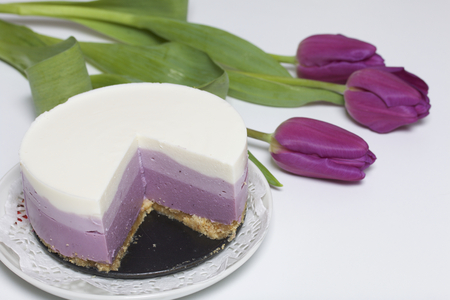 Blueberry cheesecake. A piece of ready-made dessert on a saucer. Jelly layers of different colors are visible. Near a cup of coffee and a bouquet of tulips. Stock Photo