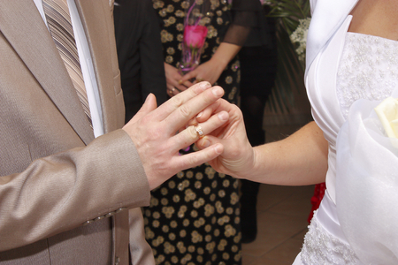 The groom in a wedding suit puts a wedding ring on the bride.