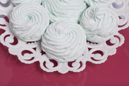 Homemade marshmallows laid on a plate. Marshmallow with mint, with a green tint. On the pink background.