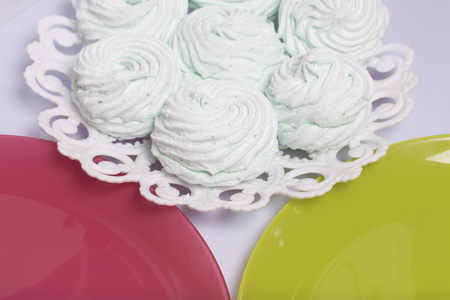 Homemade marshmallows laid on a plate. Marshmallow with mint, with a green tint. Nearby are plates of pink and light green.