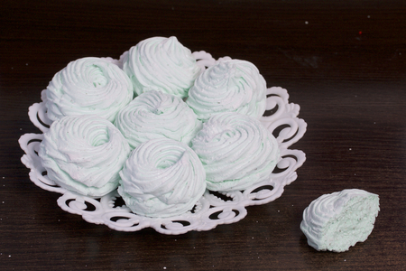 Homemade marshmallows laid on a plate. Marshmallow with mint, with a green tint. Nearby is a piece of marshmallow, its slice is visible.