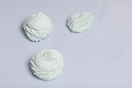 Homemade marshmallows laid on a white background. Marshmallow with mint, with a green tint. Nearby is a piece of marshmallow, its slice is visible.