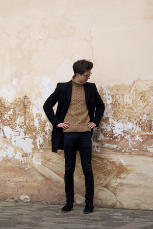 A young man with a thoughtful face poses near the untidy wall of the house. Dressed in a black light overcoat, black-rimmed glasses. On the wall are the remains of old plaster and pattern. Stock fotó