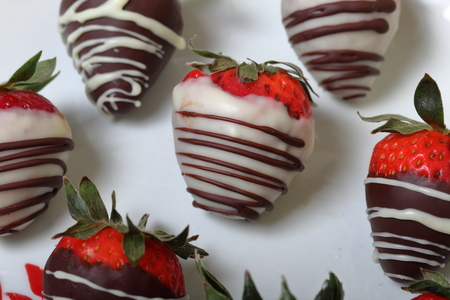 Strawberries glazed in black and white chocolate. Lie on a white plate with a pattern.