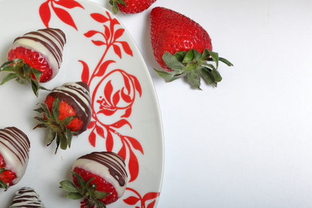 Strawberries glazed in black and white chocolate. Lie on a white plate with a pattern. Stock Photo