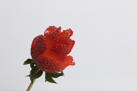 Rose flower made from strawberries. The berry is dressed on a skewer and cut with a knife.