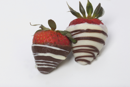 Strawberries glazed in black and white chocolate. Lie on a white background.