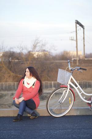 Das Mädchen sitzt neben einem geparkten Fahrrad. Ruhen Sie sich im Frühlingszyklus aus.