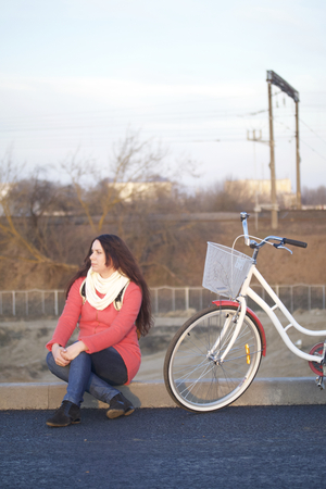 The girl sits next to a parked bike. Rest on the spring cycle.
