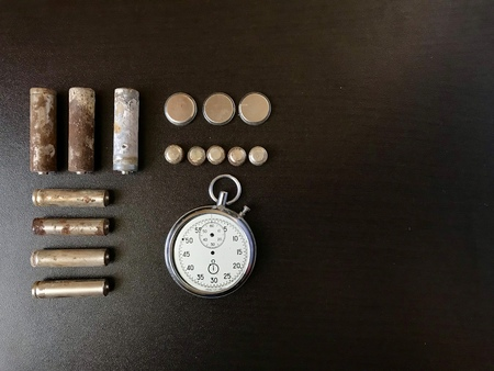 Corrosion-free batteries.  Different size and shape.  A broken stopwatch. Recycling and environmental protection.