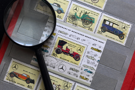 Postage stamps of the Republic of Korea in the album. Released to the 60th anniversary of Mercedes-Benz (1926-1986). Depicted various cars lineup. Near a magnifying glass for viewing.
