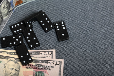 Domino knuckles on a surface covered with a coarse gray cloth. Nearby are a few dollar bills of different denominations.