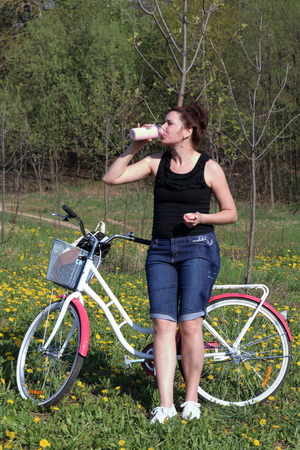 The girl leans on a parked bike. Rest on the spring cycle. The girl drinks water from a bottle.