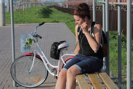 A girl sits on a bench and listens to music. Nearby is her bike. In the basket is a bouquet of flowers.