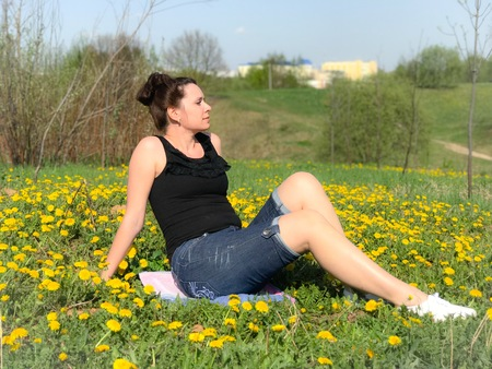 The girl is resting on the spring meadow. She is sitting on the bedspread. Dandelions are blooming, young grass is growing. Stock Photo
