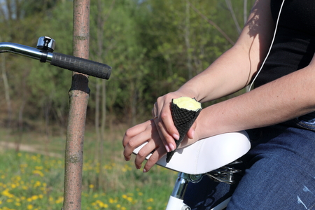 The girl is resting on the spring meadow. He sits on the trunk of the bike and eats ice cream. Dandelions are blooming, young grass is growing.
