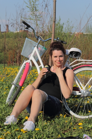 The girl is resting on the spring meadow. He sits next to the bike, eats ice cream and listens to music. Dandelions are blooming, young grass is growing.