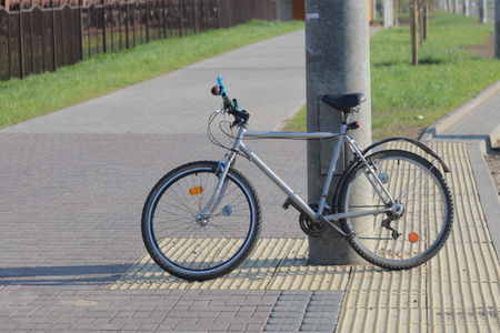 Bicycle stands near the concrete pillar. 스톡 콘텐츠