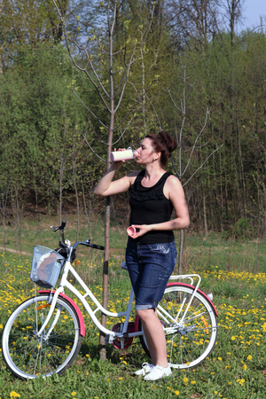 The girl is resting on the spring meadow. Standing next to the bike and drinking water. Dandelions are blooming, young grass is growing.