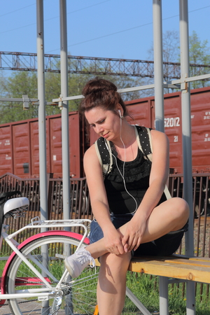 A girl sits on a bench and listens to music. Nearby is her bike.