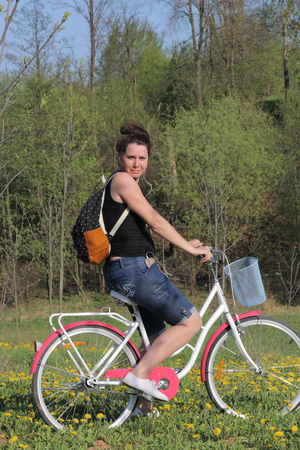 The girl is resting on the spring meadow. Sits on a bicycle, behind a tourist backpack. Dandelions are blooming, young grass is growing.
