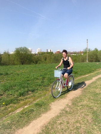 The girl is resting on the spring meadow. Riding a bike, behind a tourist backpack. Dandelions are blooming, young grass is growing.