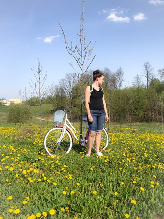 A girl stands next to a bicycle in the spring meadow. Behind her backpack. There are many flowering dandelions in the meadow. 스톡 콘텐츠