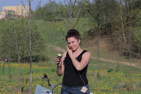 The girl is resting on the spring meadow. Standing next to the bike, eating ice cream and listening to music. Dandelions are blooming, young grass is growing.