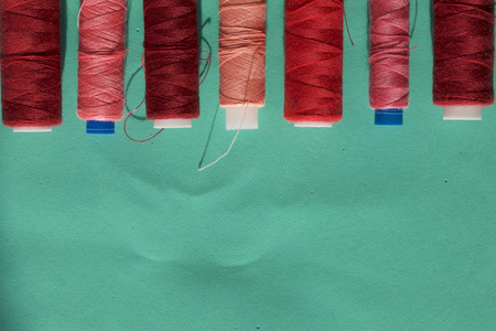 Spools of different colors are arranged in a row on a turquoise background. In the style of flat lay.