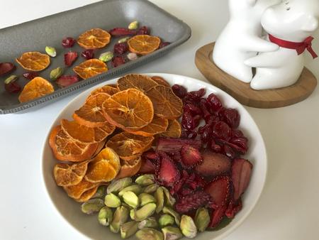 Mandarinen und Erdbeeren werden in Scheiben geschnitten und getrocknet, um Desserts zu dekorieren. Auf dem Tisch stehen auch Pistazien und getrocknete Kirschen.