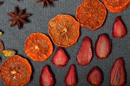 Dried tangerines and strawberries, cut into pieces to decorate the dessert. Nearby are pistachios and  anise. On a gray background.