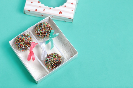 Cake Pops in chocolate with colored sprinkles. Decorated with a ribbon bow. They lie in a gift box, in the lid of which there is a transparent window.  On a mint background.