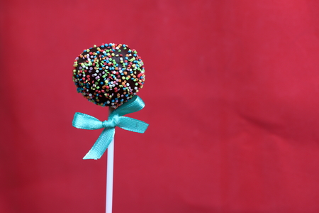 Cake Pops in chocolate with colored sprinkles. Decorated with a ribbon bow. On a red background