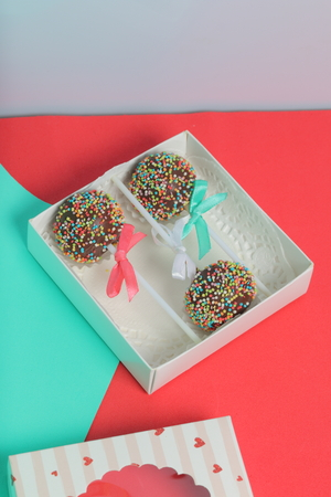 Cake Pops in chocolate with colored sprinkles. Decorated with a ribbon bow. They lie in a gift box, in the lid of which there is a transparent window.  On a red and mint background. 写真素材