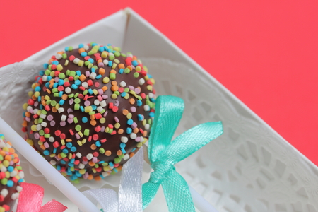 Cake Pops in chocolate with colored sprinkles. Decorated with a ribbon bow. They lie in a gift box.  On a red background.