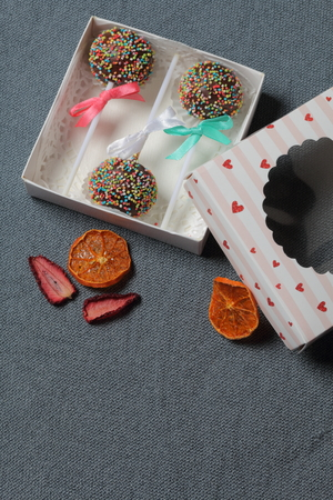 Cake Pops in chocolate with colored sprinkles. Decorated with a ribbon bow. They lie in a gift box, in the lid of which there is a transparent window. Nearby are dried fruits for decoration. On a gray background.