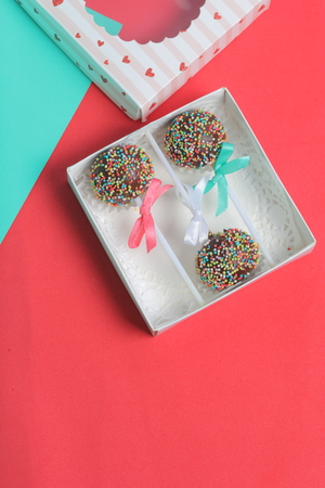 Cake Pops in chocolate with colored sprinkles. Decorated with a ribbon bow. They lie in a gift box, in the lid of which there is a transparent window.  On a red and mint background. Stok Fotoğraf