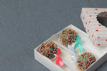 Cake Pops in chocolate with colored sprinkles. Decorated with a ribbon bow. They lie in a gift box, in the lid of which there is a transparent window.  On a gray background. Stok Fotoğraf