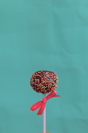Cake Pops in chocolate with colored sprinkles. Decorated with a ribbon bow. On a mint background. Stok Fotoğraf