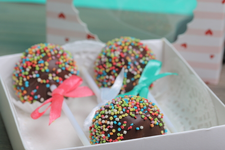 Cake Pops in chocolate with colored sprinkles. Decorated with a ribbon bow. They lie in a gift box, in the lid of which there is a transparent window.