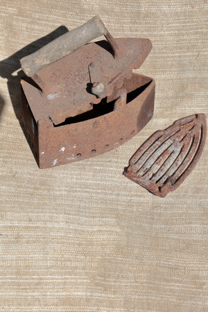 Rare iron working on coals. It stands on a coarse cloth. The iron is open, the grate is located nearby.