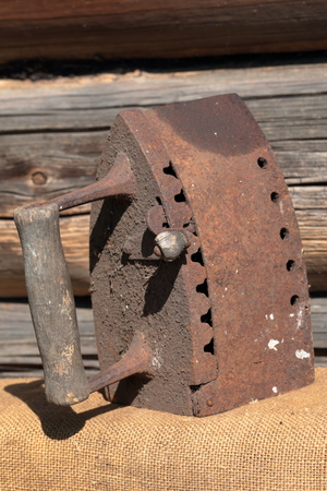 Rare iron working on coals.  It stands on the background of an old wooden barn. It stands on a coarse cloth. Stockfoto