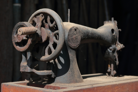 Old sewing machine, with manual drive. Covered with corrosion, dust and cobwebs. Stockfoto