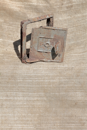 Old cast iron door for the stove. It stands on a coarse cloth. Stockfoto
